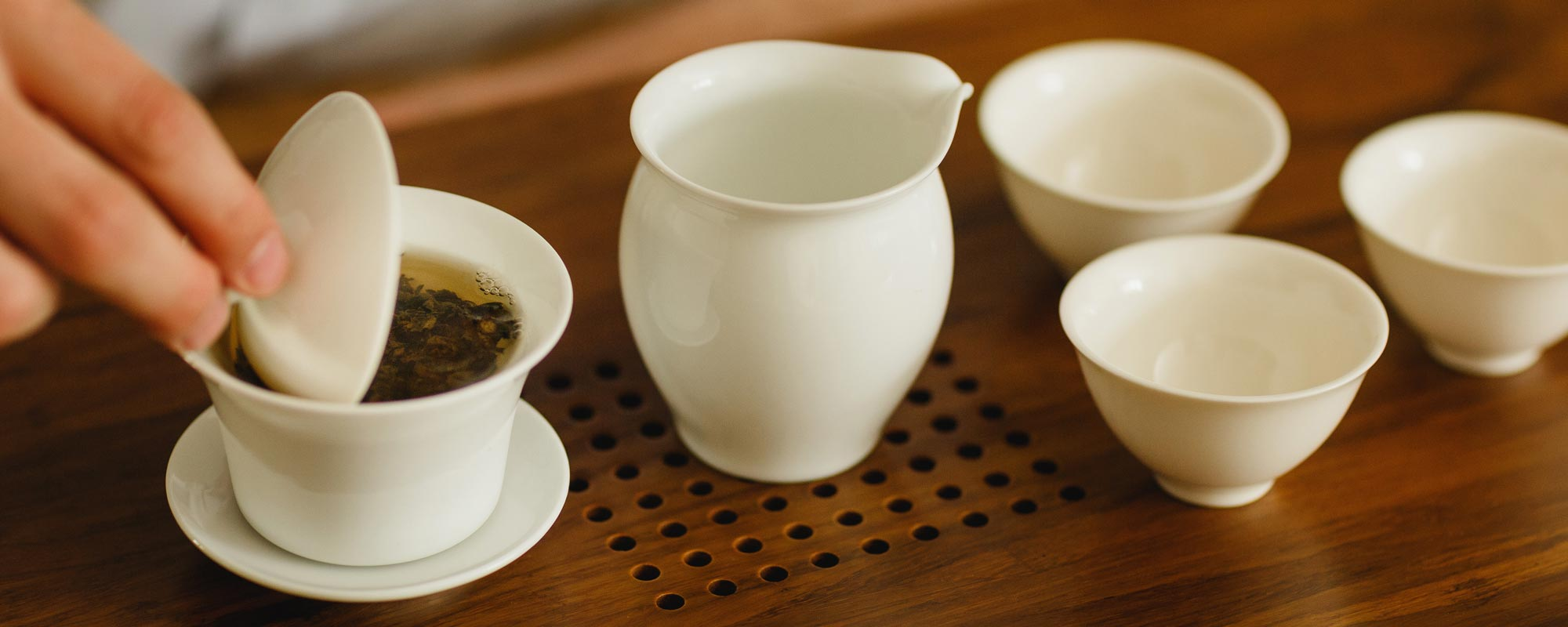 Traditional Chinese Gong Fu ceremony with porcelain gaiwan, pitcher and tea tasting cups