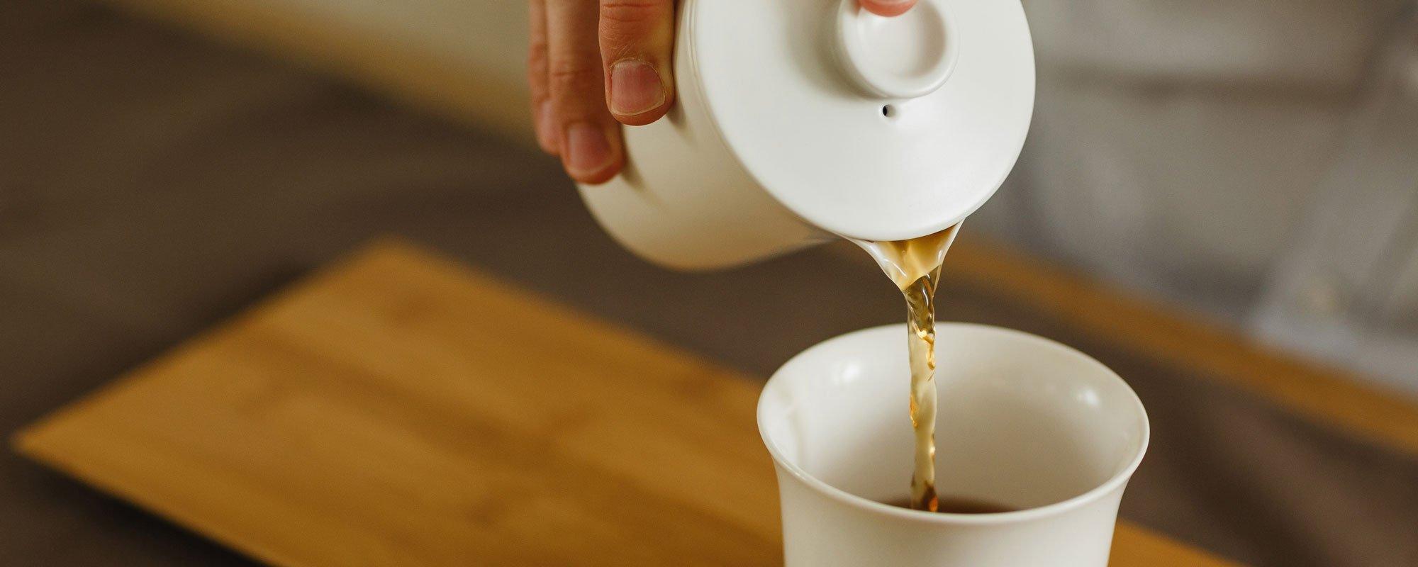 Porcelain Teapot pouring into porcelain cup