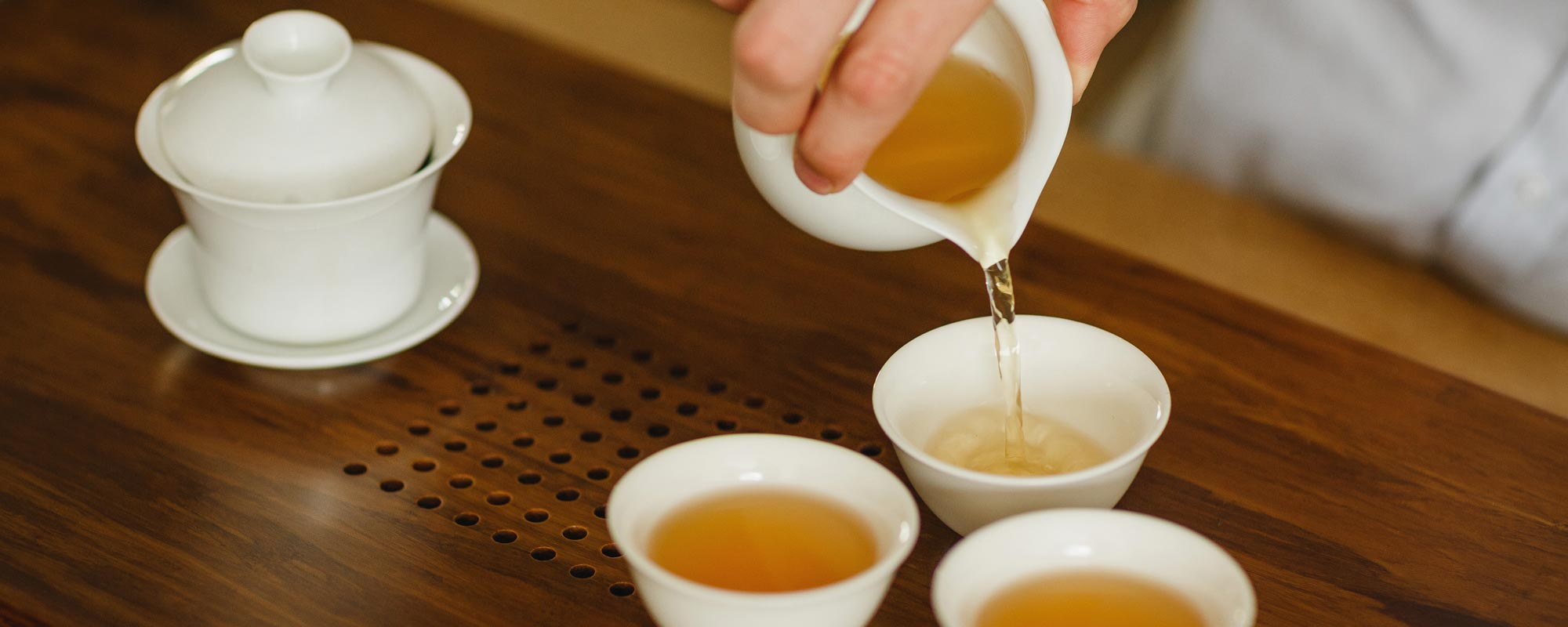 Pouring freshly made Wuyi Oolong into procelain tea tasting cups