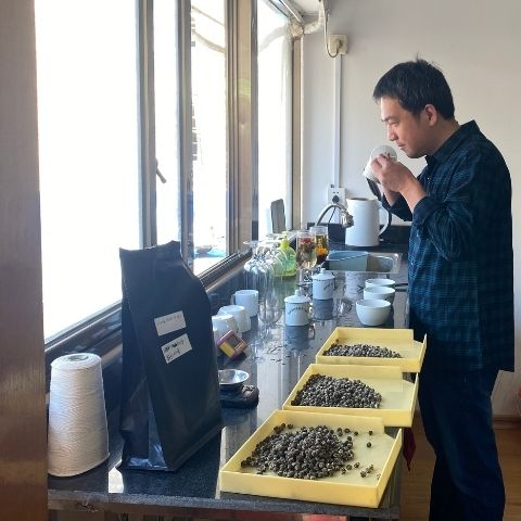 Tea maker Liu Guoqing tasting his freshly made batches of Jasmine Pearls