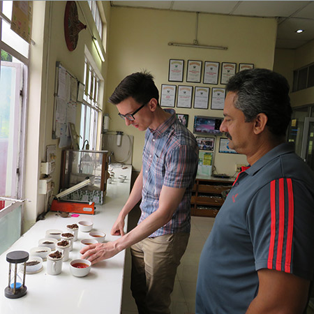 om, head of tea, tastes his way through some fresh teas with Mr. Satyajit Bhuyan, manager of Harmutty Tea Estate.
