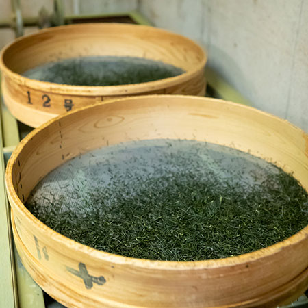 Tea leaves being slowly dried to lock in the high sweetness and deep umami.