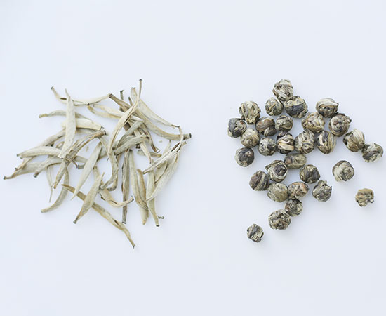 Dry Leaf - Jasmine Silver Needle (L) is a white tea made with delicate, fine buds, while Jasmine Pearls (R) is a green tea that's individually hand rolled.