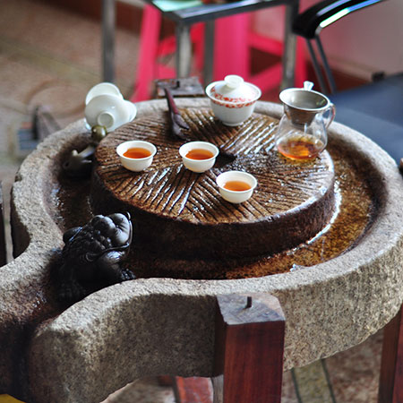 The locals drink their tea in the Gong Fu style, using a gaiwan and small cups.